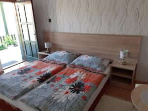 A bed or beds in a room at Hajnalka vendégház
