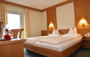 A bed or beds in a room at Hotel Crystal - Das Alpenrefugium
