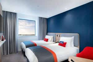 A bed or beds in a room at Holiday Inn Express - London Heathrow T4, an IHG Hotel