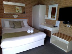 A bed or beds in a room at Country Home Motor Inn