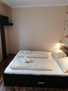 A bed or beds in a room at Major Panzió és Étterem