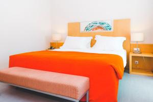A bed or beds in a room at Hotel Praia