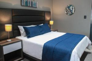 A bed or beds in a room at The Cato Suites Hotel