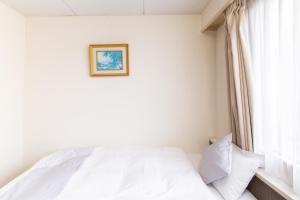 A bed or beds in a room at OYO Joetsu City Hotel Kasugayama