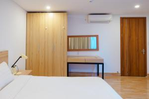 A bed or beds in a room at Domi Danang Beach Hotel