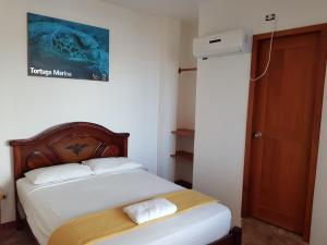 A bed or beds in a room at Gloria - Galápagos Inn