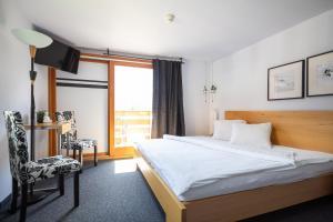 سرير أو أسرّة في غرفة في Hotel Lauberhorn - Home for Outdoor Activities