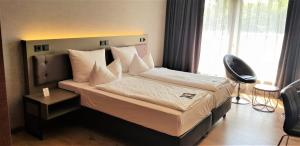 A bed or beds in a room at Michel Hotel Frankfurt Maintal