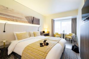 A bed or beds in a room at Mercure Oostende