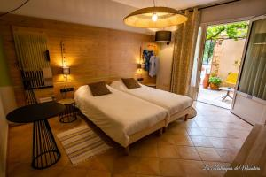 A bed or beds in a room at Hotel Les Restanques De Moustiers