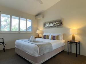 A bed or beds in a room at Byron Quarter Apartments