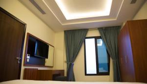 Uma TV ou centro de entretenimento em Rama Yanbu Hotel-Suite