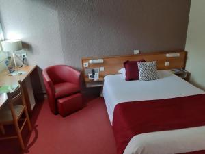 A bed or beds in a room at Logis Hôtel Atrium Epinal