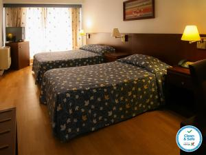 A bed or beds in a room at Albergaria Quim Barreiros