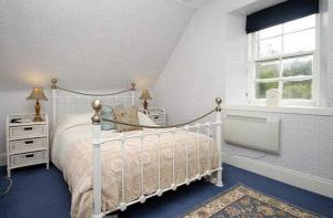 A bed or beds in a room at Coachman's Cottage