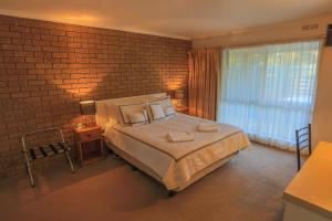A bed or beds in a room at Mountain View Motor Inn & Holiday Lodges