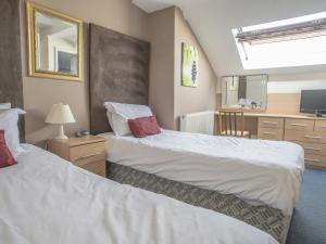 A bed or beds in a room at Baytrees Hotel
