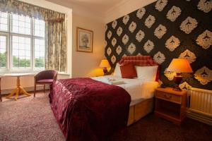 A bed or beds in a room at Westone Manor Hotel