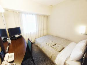 A bed or beds in a room at Takaoka Manten Hotel Ekimae