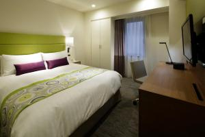A bed or beds in a room at ANA Holiday Inn Sapporo Susukino, an IHG Hotel