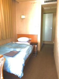 A bed or beds in a room at Asahi City Inn Hotel