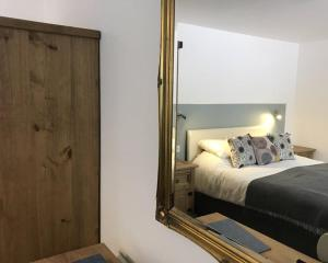 A bed or beds in a room at The Coach and Horses Hotel