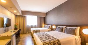 Cama ou camas em um quarto em Tauá Hotel & Convention Atibaia