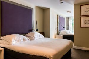 A bed or beds in a room at Hotel Roemer Amsterdam