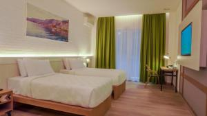 A bed or beds in a room at Jambuluwuk Convention Hall & Resort Batu