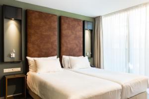 A bed or beds in a room at Hotel De Hallen