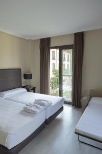 A bed or beds in a room at Hotel Real Balneario Carlos III