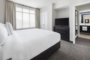 A bed or beds in a room at Residence Inn Long Island Garden City