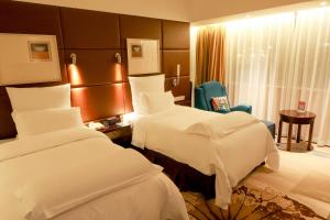 A bed or beds in a room at Pullman Guangzhou Baiyun Airport