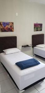 A bed or beds in a room at Pousada e Posto Amigão