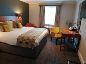 A bed or beds in a room at Best Western Plus Angel Hotel