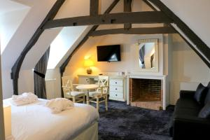 A television and/or entertainment centre at Best Western Le Cheval Blanc -Centre- Vieux Port