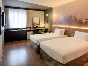 A bed or beds in a room at Mercure Curitiba Aeroporto