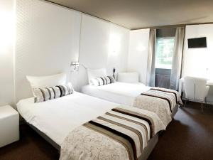 A bed or beds in a room at Hotel Woudschoten