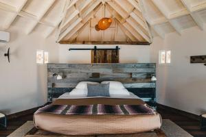 A bed or beds in a room at Thatch Caye Resort a Muy'Ono Resort
