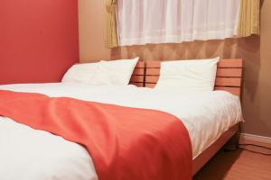 A bed or beds in a room at Petanige 今里