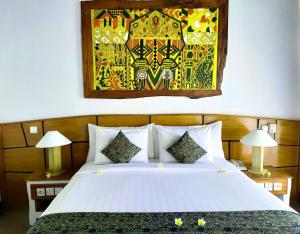 A bed or beds in a room at The Trawangan Resort