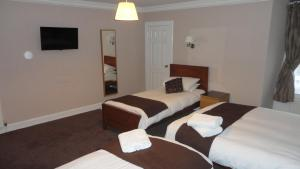 A bed or beds in a room at Sandyford Lodge