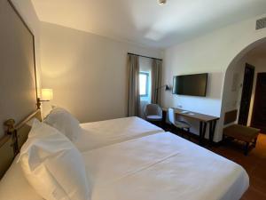 A bed or beds in a room at Parador de Jaén