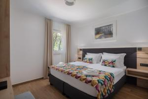 A bed or beds in a room at Noemia Family Resort