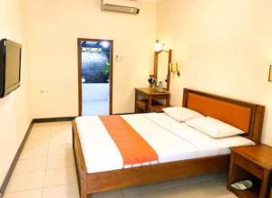 A bed or beds in a room at Peti Mas Hotel Malioboro