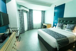 A bed or beds in a room at Bay Area Suites Manila - Quarantine Hotel