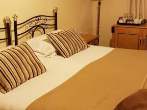 A bed or beds in a room at The Bull Hotel