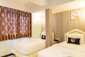 A bed or beds in a room at RoomQuest Suvarnabhumi Airport