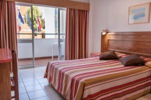 Een bed of bedden in een kamer bij Aparthotel Calema Avenida Jardim
