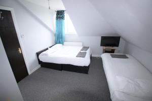 A bed or beds in a room at Clock House Hotel - London Croydon
